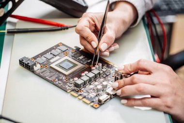 woman repairing computer hardware in service center