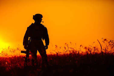 military soldier with weapons at sunset. shot, holding gun, colo