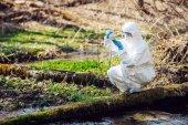 Fotografie Detailní záběr ženské vědec zkoumá tekutého obsahu baňky v lese. Ekologie a znečištění životního prostředí koncepce