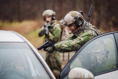 soldier points gun at suspicious car passenger. anti terrorism m