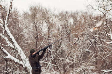 Male hunter in camouflage, armed with a rifle, standing in a sno