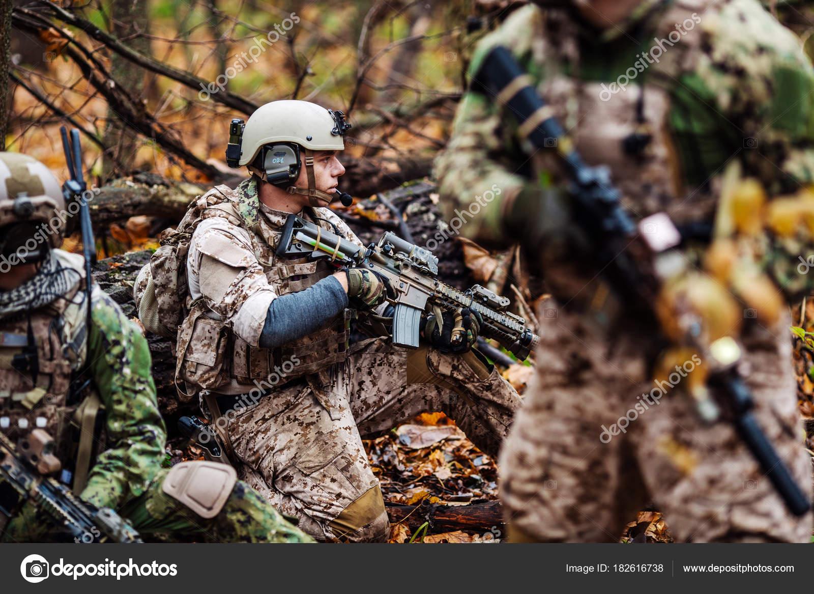 フル装備でライフルを持った兵士。背景に軍人 — ストック写真