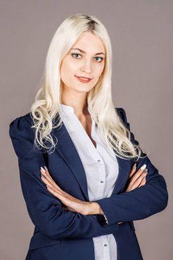 smiling businesswoman standing with crossed arms. business, education and office concept