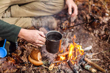 man traveler hands holding mug with water near the fire outdoors