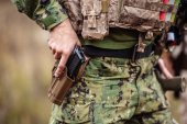 Fotografie Ranger in Uniform mit Gewehr in der hand halten Waffe im holster