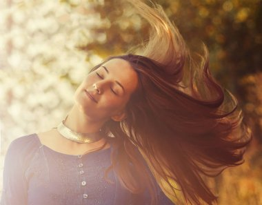Beautiful woman with long hair in nature.