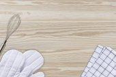 Fotografia Guanti bianchi di cottura, frullatore tovagliolo e uovo su tavola di legno backg