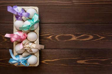 Easter eggs are tied in bows of color ribbons in the box on the wooden background