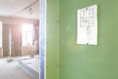 Sheet of project on the wall and construction worker install plasterboard drywall in apartment is under construction, remodeling, renovation, extension, restoration and reconstruction.