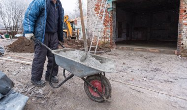 Worker in protect gloves is holding the building trolley with sand to making the concrete in construction site. Concept of using of construction materials during construction, remodeling, renovation