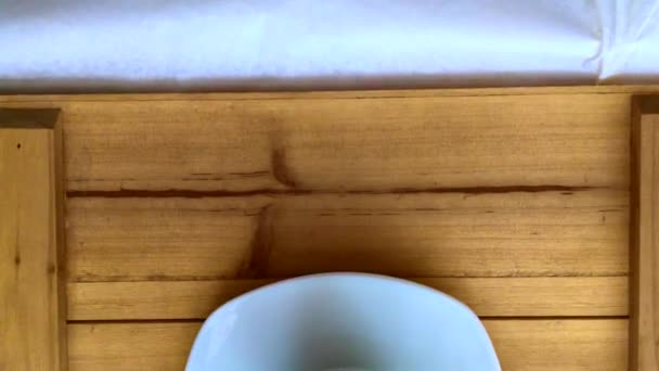 White cup with black coffee on wooden table