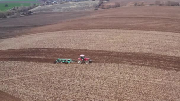 Farmer plows a field, preparing land for sowing. Tractor cultivates the soil on the farm at springtime for plant agriculture. Aerial view footage of agribusiness in the countryside in the spring.
