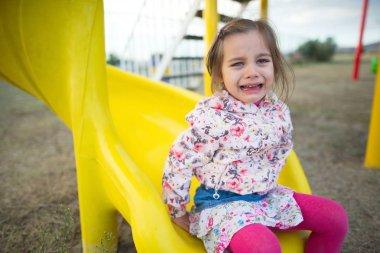 Little Girl Swinging At Playground