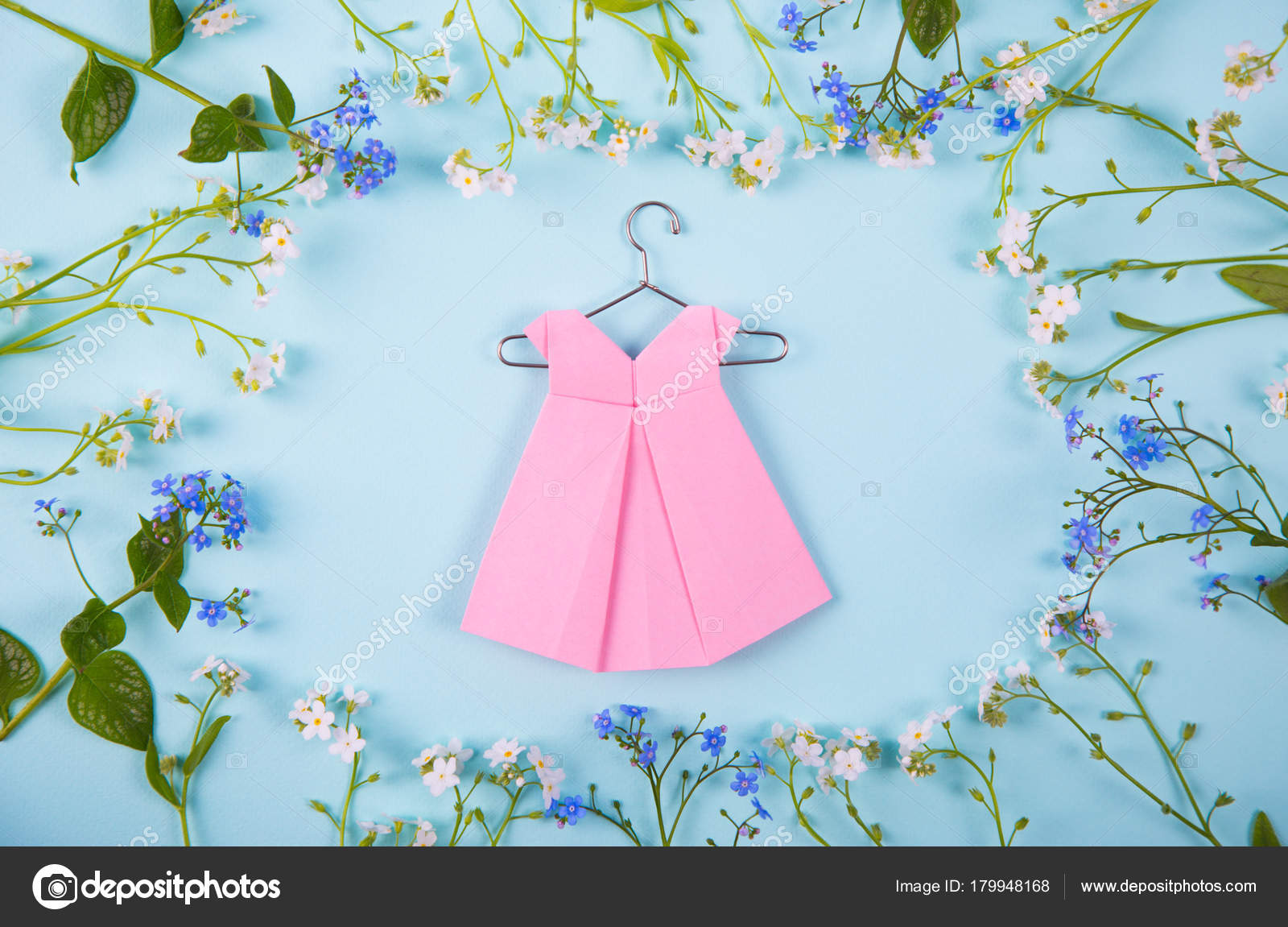 Paper origami dress on hanger surrounded with blue and white lit paper origami dress on hanger surrounded with blue and white lit stock photo jeuxipadfo Choice Image