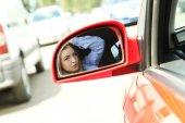 Szép fiatal lány arcát autó tükörben