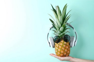 Female hand holding pineapple with sunglasses and headphones