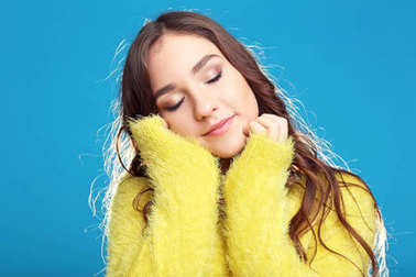 Beautiful young girl in yellow sweater on blue background