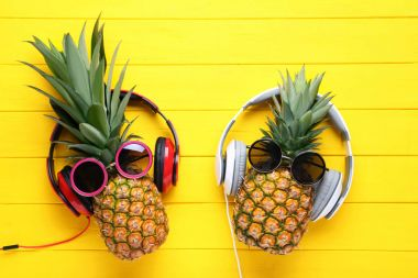 Ripe pineapples with sunglasses