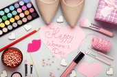 Inscription Happy womens Day with high-heeled shoes and makeup cosmetics