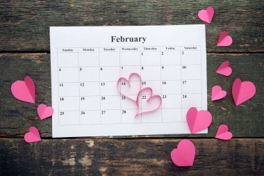Pink hearts with february calendar on wooden table
