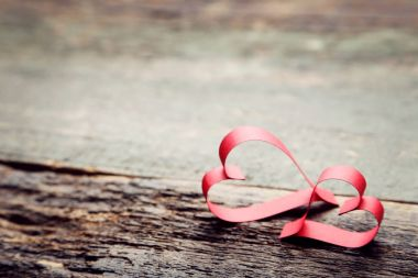 Red paper hearts on grey wooden table