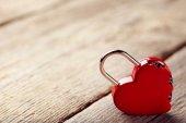 Visací zámek na šedý dřevěný stůl ve tvaru srdce