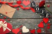 Szív, vörös rózsa, ajándék doboz és a fából készült asztal boríték