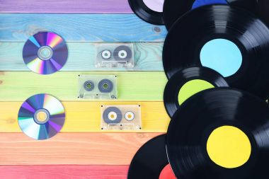 Vinyl records with cassette tapes and CD disk on colourful wooden table