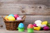 Barevné velikonoční vejce v košíku s tulipány na šedý dřevěný stůl