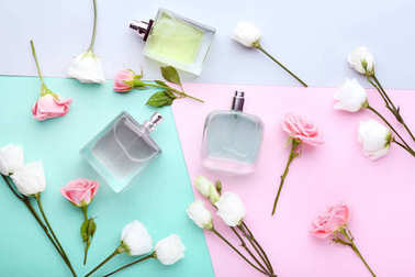 Perfume bottles with flowers on colorful background