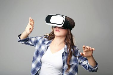 Young girl in virtual reality goggles on grey background