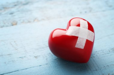 Red heart with adhesive bandage on blue wooden table