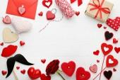 Fotografie rote und weiße Herzen mit Kerzen und Geschenkkarton auf weißem Holztisch