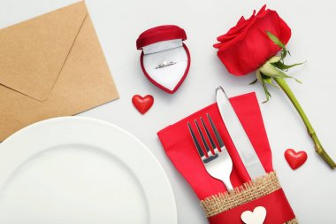 Kitchen cutlery with envelope, silver ring and red rose on grey background stock vector