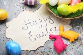 Inscription Happy Easter with painted eggs and fabric rabbits on grey wooden table