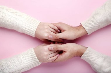 Female and male hands holding each other on pink background
