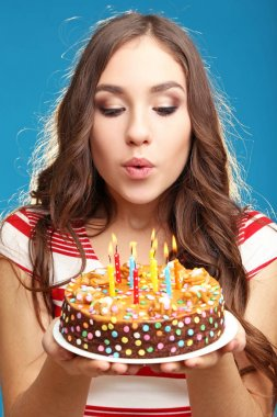 Young woman blowing out candles on birthday cake