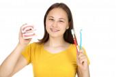 Fotografie junges Mädchen mit Zahnspange mit Zahnmodell und Zahnbürste