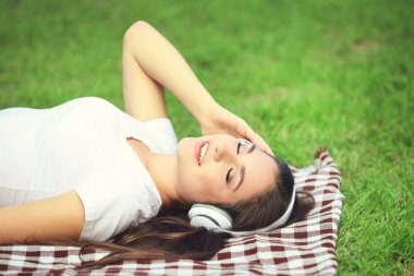 Young happy girl lying on green grass and listening music with h
