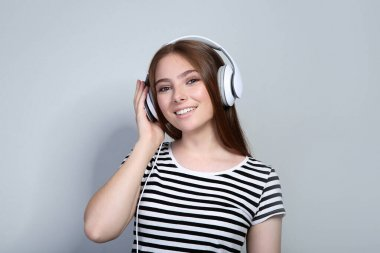 Young woman with headphones on grey background