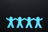 Fotografie Papierkettenmenschen auf schwarzem Hintergrund
