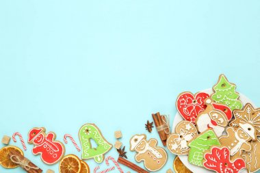 Christmas gingerbread cookies with candies, cinnamon and sugar on blue background