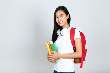 Young woman with books, headphones and backpack on grey backgrou