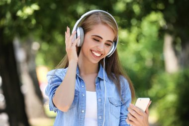 Young smiling girl listening music with headphones and using sma