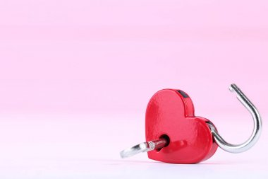 Valentine heart shaped padlock and key on pink background