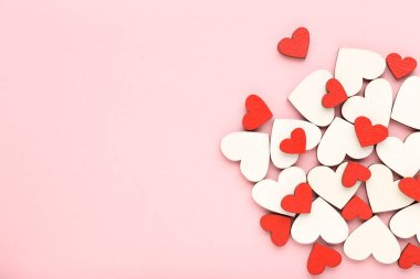 Wooden white and red hearts on pink background