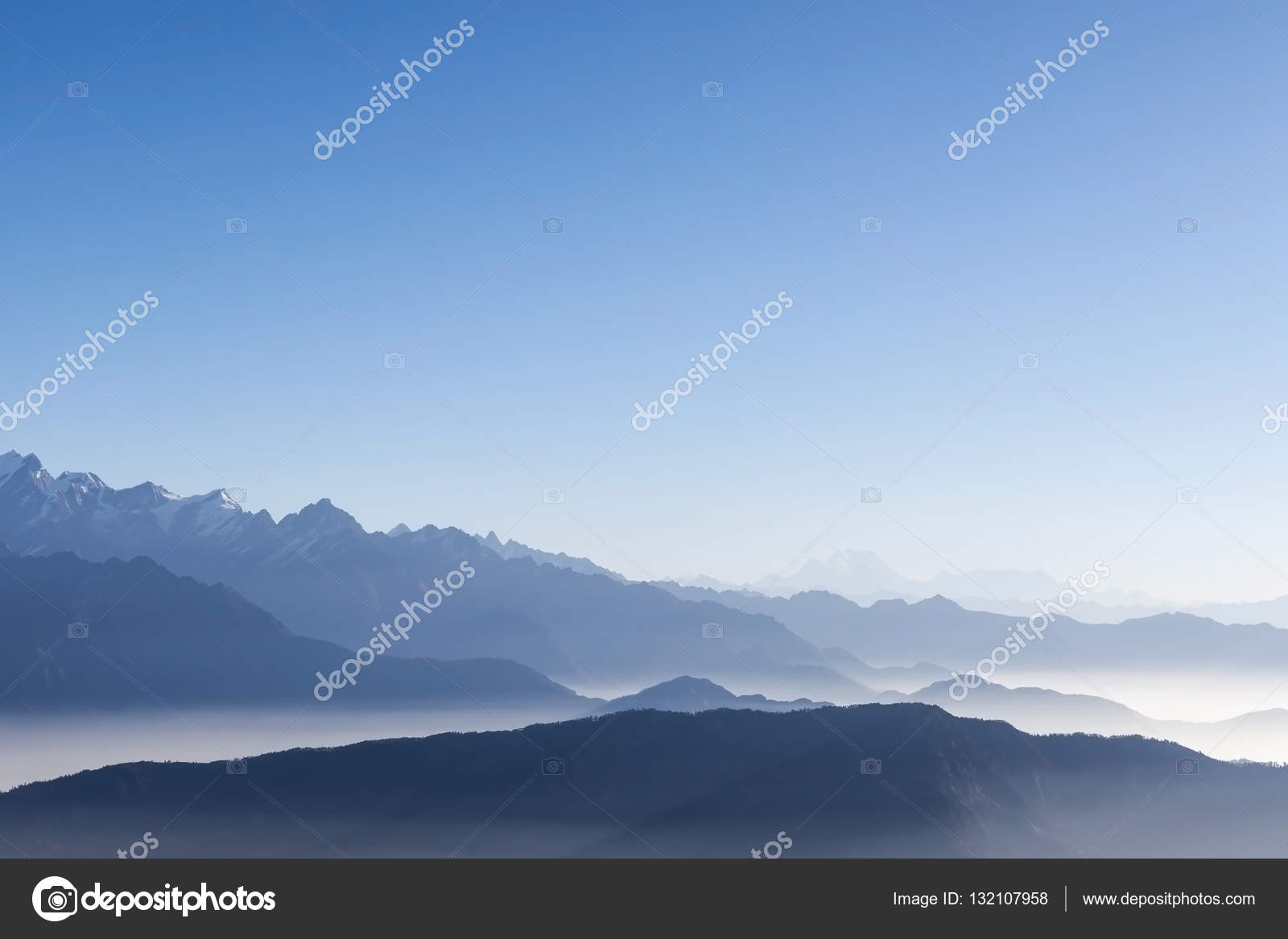 foggy mountain range background with blue sky and white