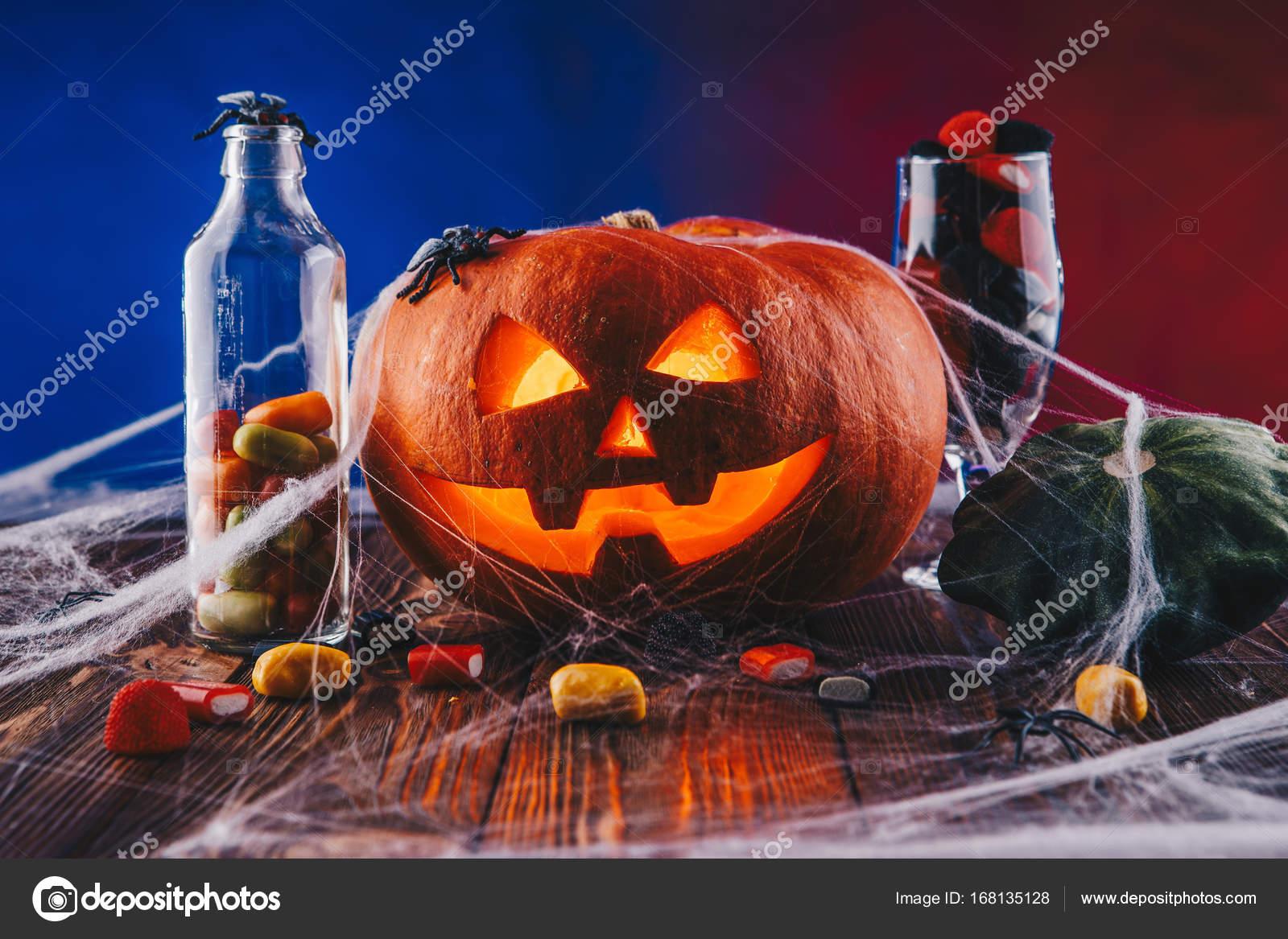 Zucca di halloween in una ragnatela con dolci e illuminazione