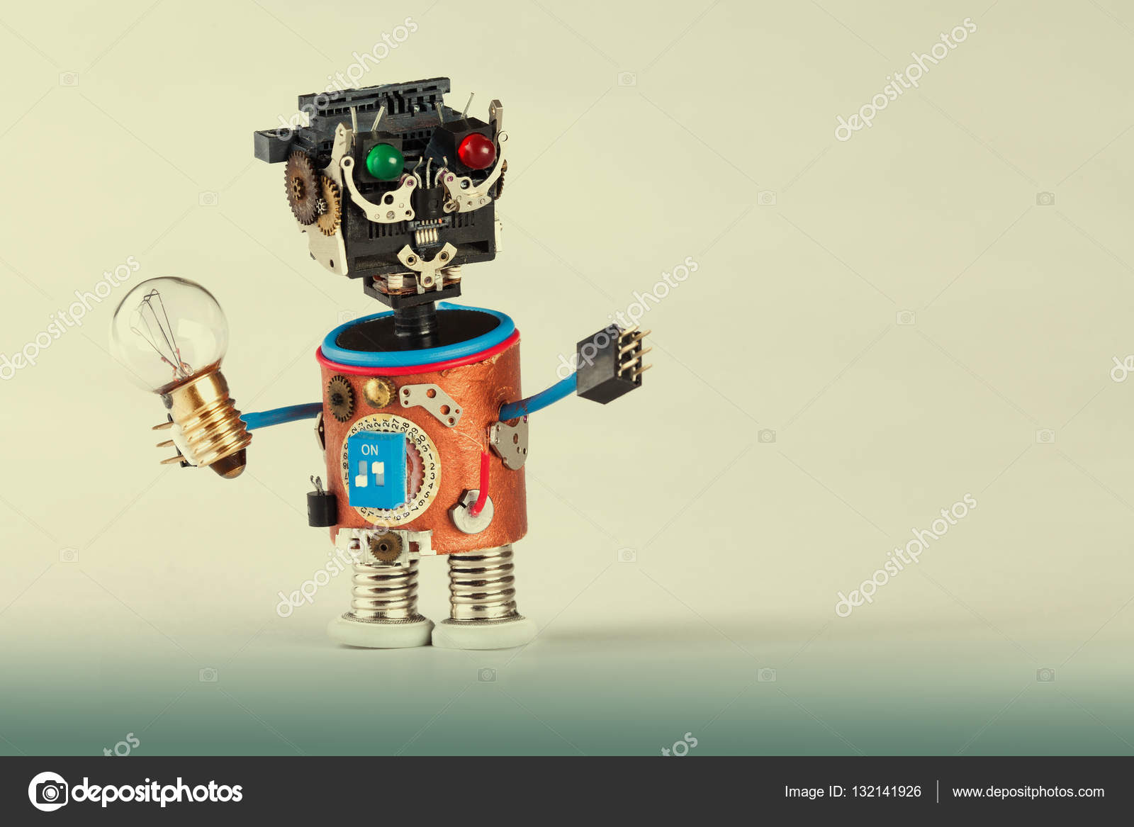 Mechanical robot with light bulb. Plastic head, colored green red ...