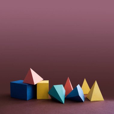 Colorful platonic solids, abstract geometric figures on violet background. Pyramid prism rectangular cube yellow blue pink green colored shapes. Shallow depth of field, copy space.